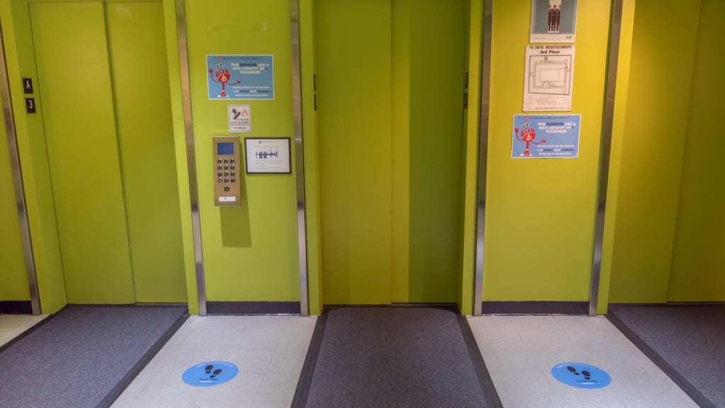Social distance stickers are clearly marked in elevators, lobbies, and on floors