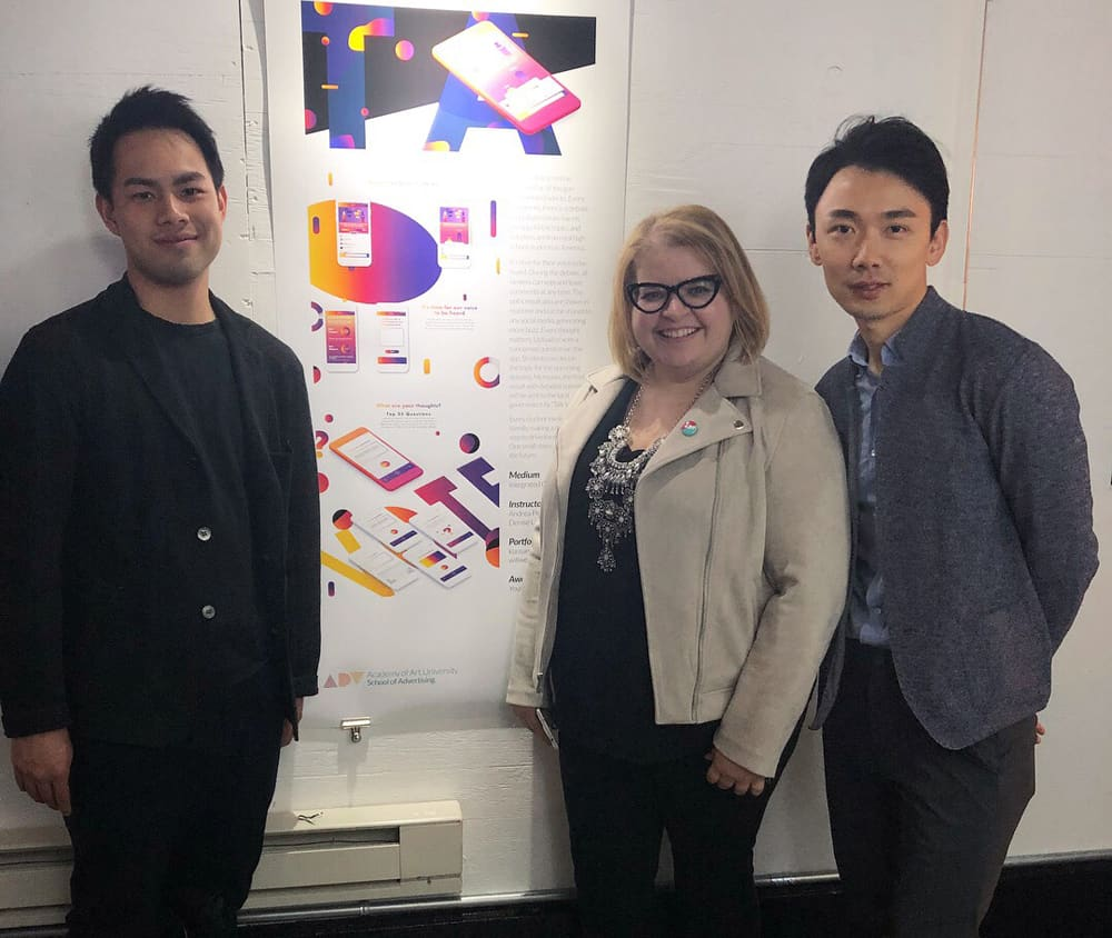School of Advertising alumni Hsiu Chi (Sam) Kuo and Wei (Will) Wang with Advertising and Web Design & New Media Co-director Andrea Pimantel (center). They're standing before a project awarded in the Young Glory advertising competition.